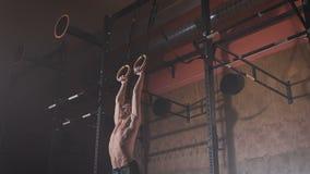 Jonge mens in een goede vorm die oefeningen spier-UPS op de sportringen doen bij de gymnastiek stock video