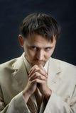 Jonge mens in een kostuum, dat voor iets bidt Stock Foto's
