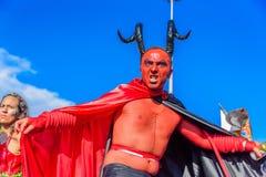 Jonge mens in een kostuum van duivel met rood gezicht, zwarte hoornen en mantel die op stelten in Bloco Orquestra Voadora, Carnav Stock Foto's