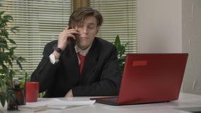 Jonge mens in een kostuumzitting in het bureau, die op de telefoon, smartphone spreken, die ja door hoofd, overeenkomst tonen te  stock video