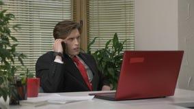 Jonge mens in een kostuumzitting in het bureau, die op de telefoon, smartphone, vermoeid sarcasme spreken, Het werk in het bureau stock videobeelden