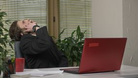Jonge mens in een kostuumzitting in het bureau, die op de telefoon, smartphone, vermoeid sarcasme spreken, Het werk in het bureau stock video