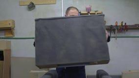 Jonge mens in een meubilairfabriek die katoen op ??n deel van de bank zet stock videobeelden