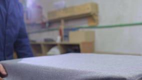 Jonge mens in een meubilairfabriek die katoen op ??n deel van de bank zet stock video