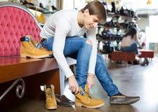 Jonge mens in een schoenopslag Stock Foto's