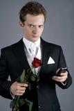 Jonge mens in een zwart kostuum met roos en phon Royalty-vrije Stock Foto's