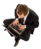Jonge mens in een zwart pak met laptop stock afbeelding