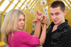 Jonge mens en blonde in handcuff stock foto's
