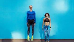Jonge mens en leuk meisje die op blauwe achtergrond springen stock afbeeldingen