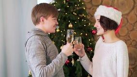 Jonge mens en meisje die en met glazen die champagne spreken glimlachen zich dichtbij Kerstmisboom bevinden De stemming van Kerst stock video