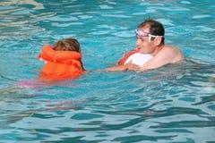 Jonge mens en meisje in reddingsvest het baden in pool royalty-vrije stock foto's