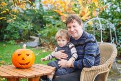 Jonge mens en peuterjongen die Halloween pompoen maakt Royalty-vrije Stock Afbeelding