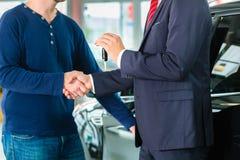 Jonge mens en verkoper met auto in het autohandel drijven royalty-vrije stock afbeeldingen