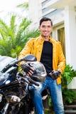 Jonge mens en zijn motorfiets of autoped stock fotografie