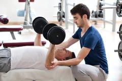 Jonge mens en zijn vader in de gymnastiek Royalty-vrije Stock Afbeelding