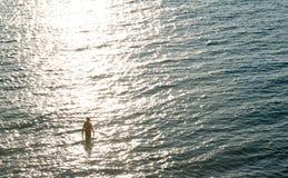 Jonge mens en zonsopgang op overzees Royalty-vrije Stock Foto's