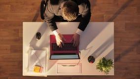 Jonge mens in glazen en kostuum die in het openen komen en op laptop typen, die achter bureau, hoogste schot zitten stock videobeelden