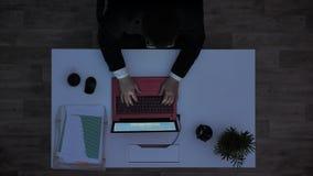 Jonge mens in glazen en kostuumzitting achter op laptop typen en bureau die, die hoogste schot, schot van dag die draaien aan weg stock videobeelden