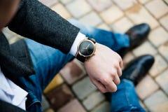 Jonge mens in grijze jasje en jeans, elegante bedrijfsmensen` s hand Royalty-vrije Stock Afbeeldingen