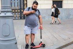 Jonge mens in grijze t-shirt en borrels die smartphone en een autoped van kinderen houden royalty-vrije stock fotografie