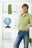 Jonge mens in groen bureau Stock Afbeeldingen