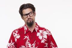 Jonge mens in Hawaiiaans overhemd met opgeheven wenkbrauw die bevinden zich tegen Stock Fotografie