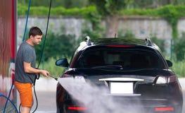 Jonge mens het bespuiten van zijn auto royalty-vrije stock foto's