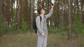 Jonge mens in het bos die een mobiel signaal proberen te vangen stock footage
