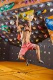 Jonge mens het bouldering in binnen het beklimmen gymnastiek stock afbeeldingen