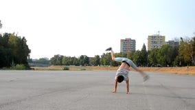 Jonge mens het dansen breakdance op de straat stock footage