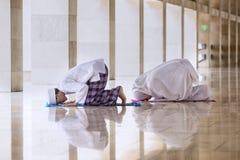 Jonge mens het doen bidt met zijn vrouw in de moskee stock foto's