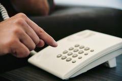 Jonge mens het draaien op een landline telefoon stock afbeeldingen