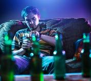 Jonge mens het drinken alleen bier Stock Foto's