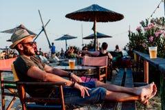Jonge mens het drinken bier in een strandbar royalty-vrije stock foto