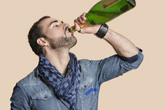 Jonge mens het drinken champagne van fles over gekleurde achtergrond Royalty-vrije Stock Afbeelding