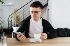 Jonge mens het drinken koffie in koffie en het gebruiken van telefoon stock afbeeldingen
