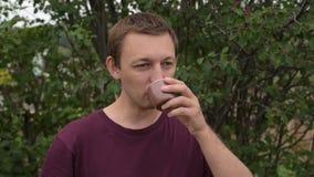 Jonge mens het drinken thee in openlucht stock footage