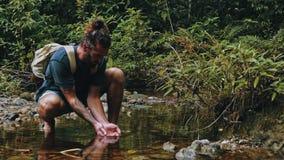 jonge mens het drinken van de glasheldere rivier in het midden van het tropische wildernisregenwoud stock foto