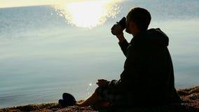 Jonge mens het drinken van kop op een strand stock footage