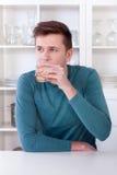 Jonge mens het drinken verfrissende limonade in zijn keuken royalty-vrije stock afbeeldingen