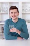 Jonge mens het drinken verfrissende limonade in zijn keuken stock afbeelding