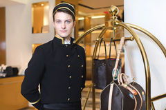 Jonge mens in het eenvormige dienen in hotel Stock Foto's