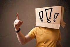 Jonge mens het gesturing met een kartondoos op zijn hoofd met exclam Royalty-vrije Stock Foto's