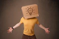 Jonge mens het gesturing met een kartondoos op zijn hoofd met licht Stock Fotografie
