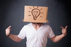 Jonge mens het gesturing met een kartondoos op zijn hoofd met licht Stock Afbeeldingen