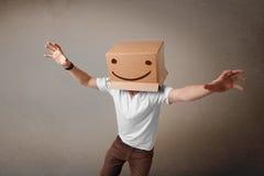 Jonge mens het gesturing met een kartondoos op zijn hoofd met smiley Stock Foto's