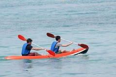 Jonge mens het kayaking onderaan een overzees Stock Afbeelding