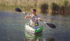 Jonge mens het kayaking op het meer stock afbeelding