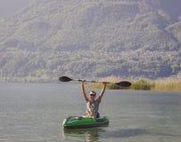 Jonge mens het kayaking op het meer stock foto