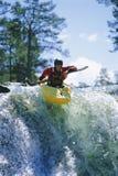 Jonge mens het kayaking op waterval Stock Foto's
